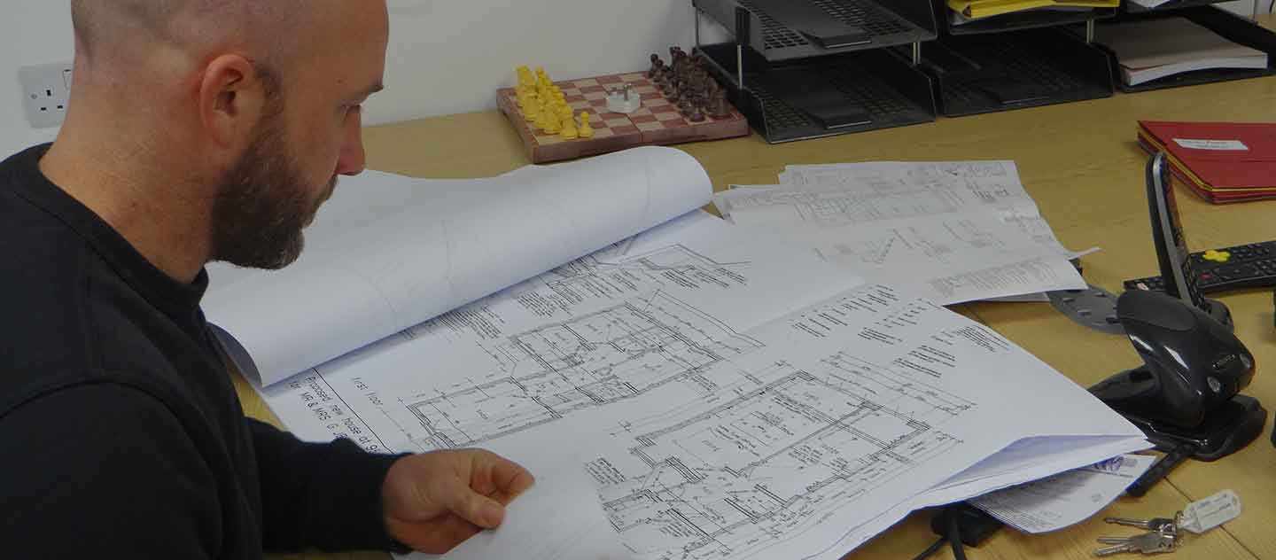 Dan Gruncell studying architects drawing.